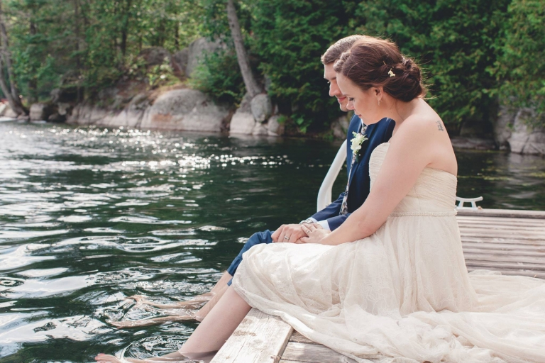 bride and groom sitting on the dock after wedding